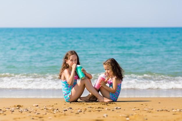 Meisjes zitten tegenover elkaar en drinken uit gekleurde mooie cocktailglazen familie vakantie concept