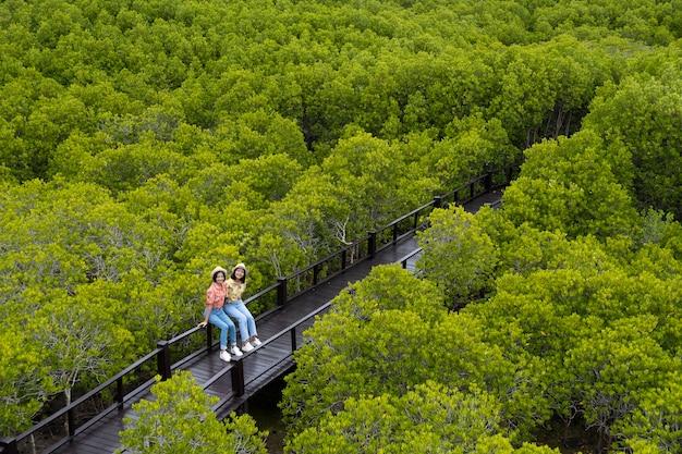 Meisjes zittend op een brug in het bos