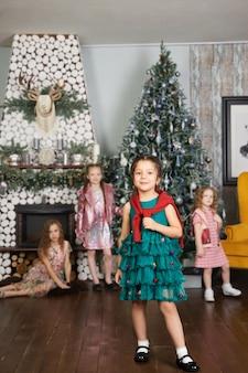 Meisjes zusters en kerstochtend, kinderen poseren tegen de achtergrond van het interieur van de kerstboom. grote familie