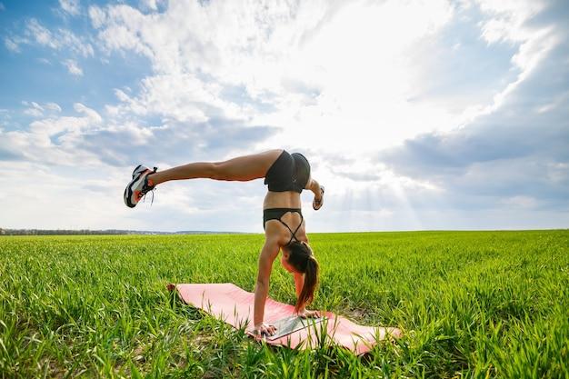 Meisjesacrobaat voert een handstand uit. het model staat op haar handen, doet gymnastische splitsingen tegen de achtergrond van groene val en blauwe lucht, sportend in de natuur