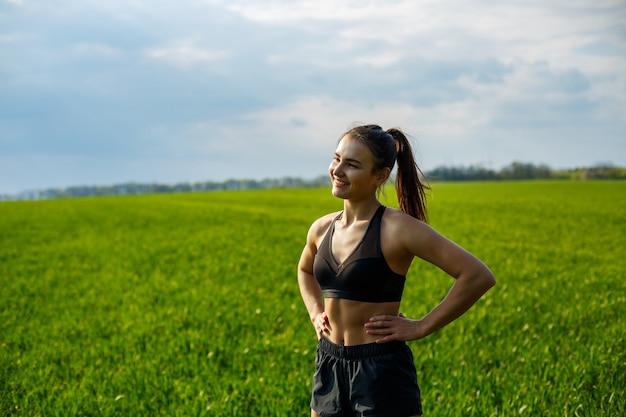 Meisjesatleet warmt buitenshuis op, oefeningen voor spieren. jonge vrouw gaat voor sport, gezonde levensstijl, atletisch lichaam. ze is in sportkleding, zwarte top en korte broek. sportconcept.