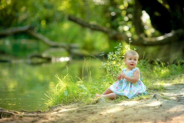 Meisjesbaby één blootvoets dichtbij water in het bos
