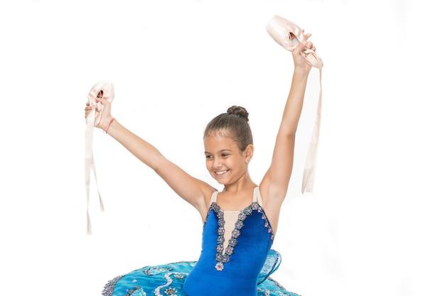 Meisjesballerina houdt pointe-schoenen in de hand witte achtergrond. er zijn veel wegen naar ballet. kind gelukkig houdt balletschoenen belangrijk kenmerk uitstekende ballerina. start carrière klassieke dansen programma.