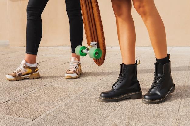 Meisjesbenen in sportschoenen en zwarte laarzen, skateboard met groene wielen.