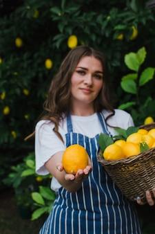 Meisjesboer met een mand houdt een citroenclose-up in haar hand focus op citroen