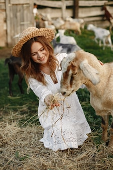 Meisjesboer met witte geit. vrouw en klein geit groen gras. eco boerderij. boerderij en landbouwconcept. dorpsdieren. meisje speelt schattige geit. f.