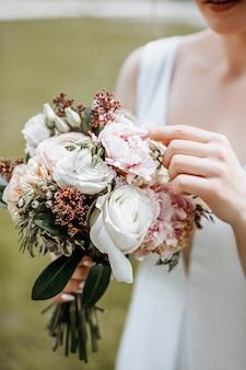 Meisjesbruid die een huwelijksboeket van bloemen houden