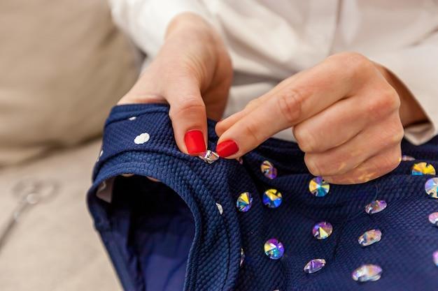Meisjesdesignerhanden met een rode manicure naaien strass-steentjes aan het blauwe zwempak