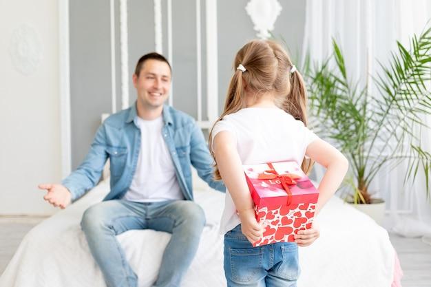 Meisjesdochter geeft een cadeau aan haar geliefde vader die het achter haar rug verbergt, gelukkige familie of vaderdag