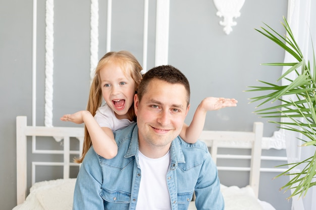 Meisjesdochter speelt plezier met vader thuis die zijn ogen sluit, gelukkige familie