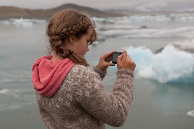 Meisjesfotograaf in een ijslandse sweater en een koraal hoodie die zich op blauwe ijsbergen in een ijzig meer concentreren