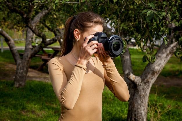 Meisjesfotograaf maakt een foto op een professionele camera in het park. meisjesfotograaf in het park