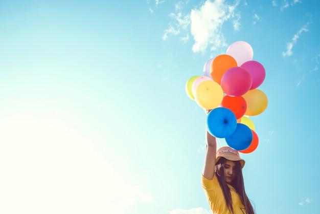 Meisjeshand die veelkleurige die ballons houden met een retro effect van de instagramfilter, concept gelukkige geboortedag in de zomer en huwelijks wittebroodswekenpartij, uitstekende kleurentoonst