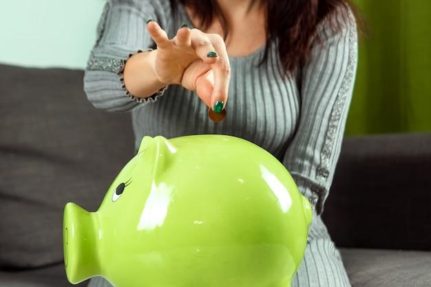Meisjeshand gooit een munt in het spaarvarken in de vorm van een groen varken