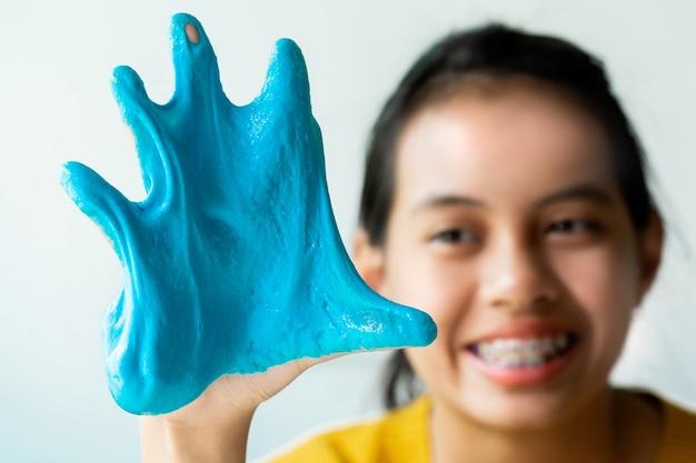 Meisjeshand met zelfgemaakt speelgoed genaamd slime,