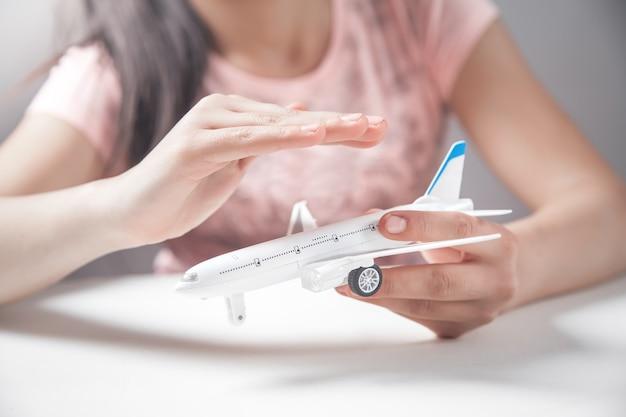 Meisjeshanden beschermen vliegtuigmodel. reizen