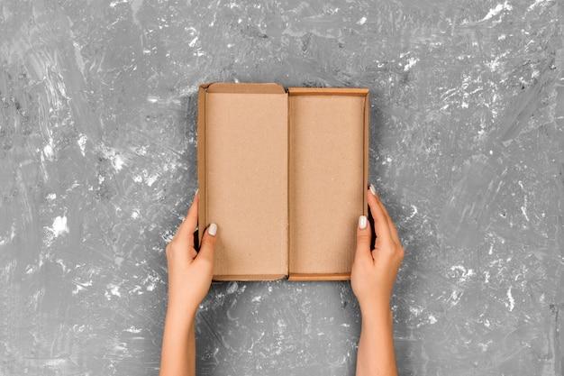 Meisjeshanden die lege doos op grijze achtergrond, hoogste mening houden