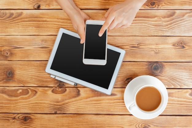 Meisjeshanden met digitale tablet en kop van koffie op een houten lijst