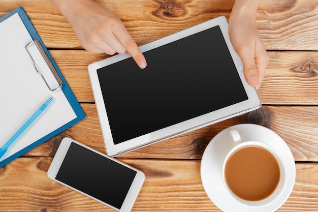Meisjeshanden met digitale tablet en kopje koffie op een houten tafel