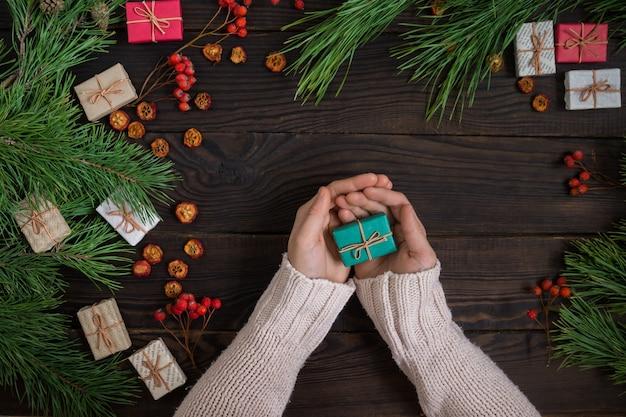 Meisjeshanden met kerstcadeau op de achtergrond van donkere planken van pijnboomtakken