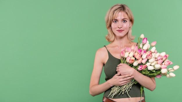 Meisjesholding bloemen en het bekijken fotograaf