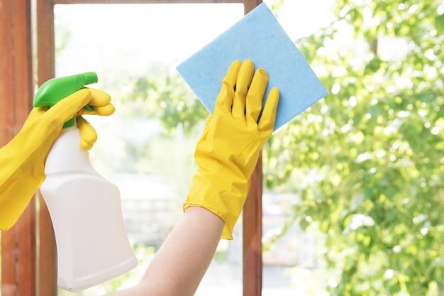 Meisjeshuisvrouw wast de ramen in het huis in gele rubberen handschoenen en met een blauwe doek