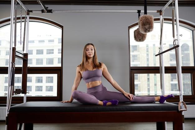 Meisjesinstructeur op reformer cadillac, poseren, oefeningen tonen voor wervelkolomcorrectie, moderne reformerapparatuur voor fitnesscentra.