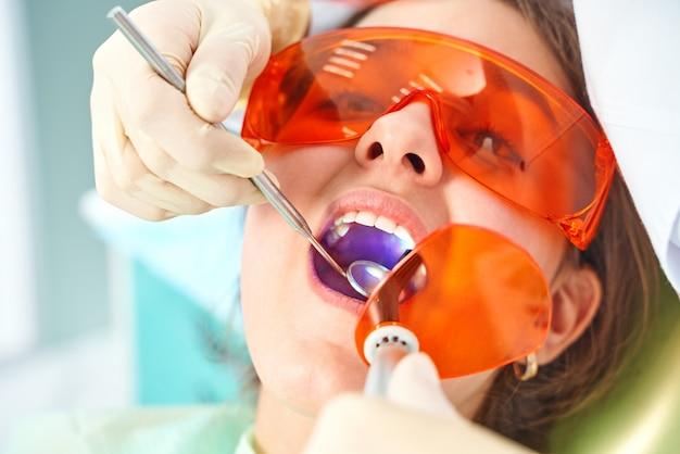 Meisjeskind bij de arts. tandarts plaatst een vulling op een tand met tandheelkundige polymerisatielamp in de mondholte. over kliniekachtergrond