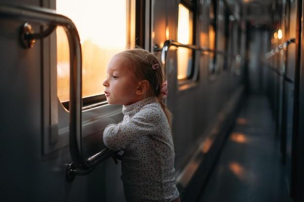 Meisjeskind dat door het treinraam kijkt bij zonsondergang