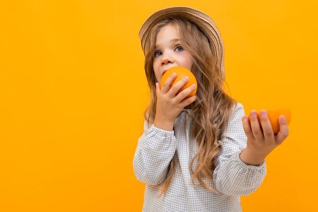Meisjeskind dat een sinaasappel op een gele achtergrond met ruimte eet.
