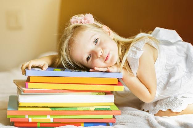 Meisjeskind dat op het bed met boeken ligt