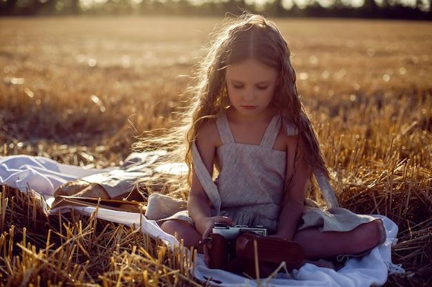 Meisjeskind in een jurk zittend op een gemaaid veld met een camera op een deken met brood en een boek