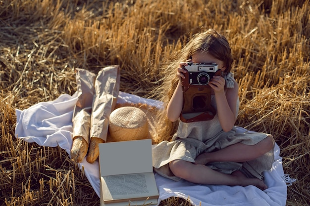 Meisjeskind in een jurk zittend op een gemaaid veld met een camera op een deken met brood en een boek Premium Foto