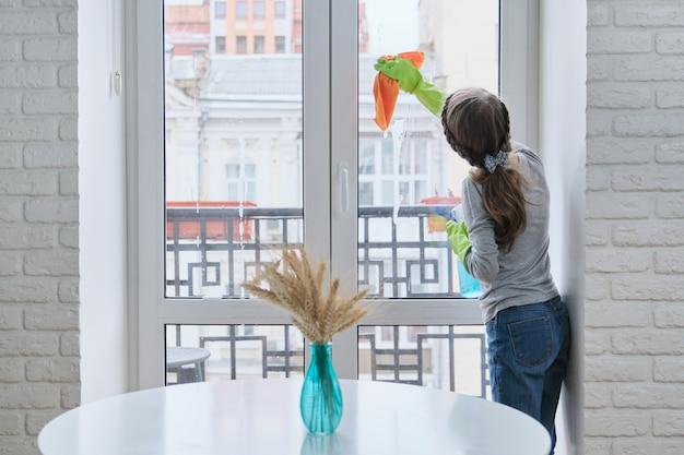 Meisjeskind in handschoenen met nevelwasmiddel met vod die huis schoonmaken