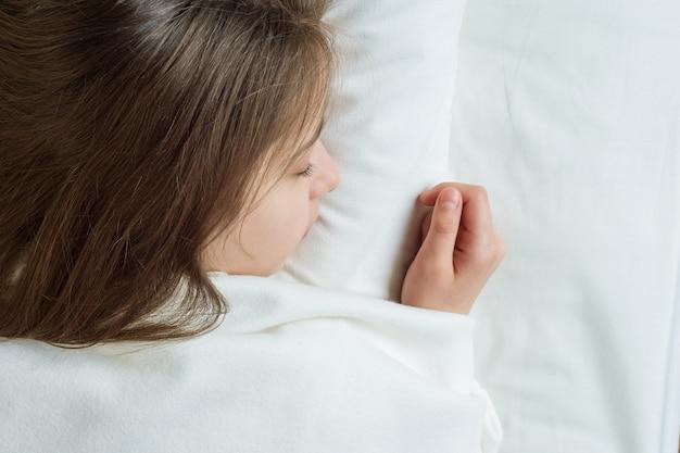 Meisjeskind met lang bruin haar slapen op een kussen in bed