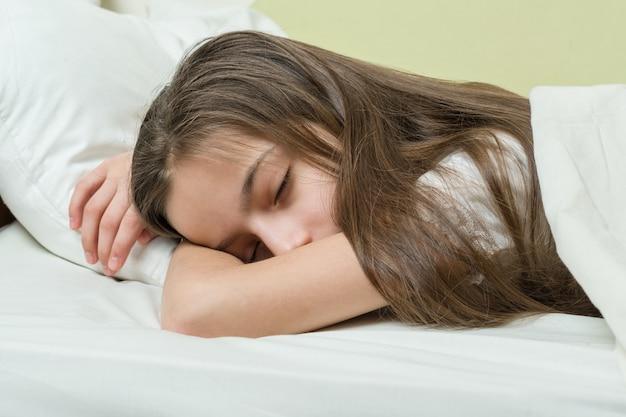 Meisjeskind met lange bruine haarslaap op hoofdkussen