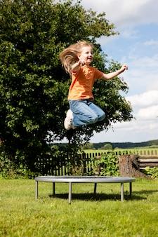 Meisjeskind op trampoline in de tuin