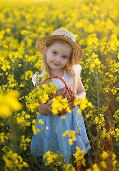 Meisjeskind verzamelt bloemen, mooie glimlach, koolzaadveld, natuur in de zomer