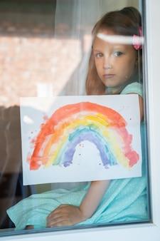 Meisjeskind zit en kijkt uit het raam met een regenboogpatroon in haar handen terwijl ze het huis isoleert van de pandemie van het coronavirus