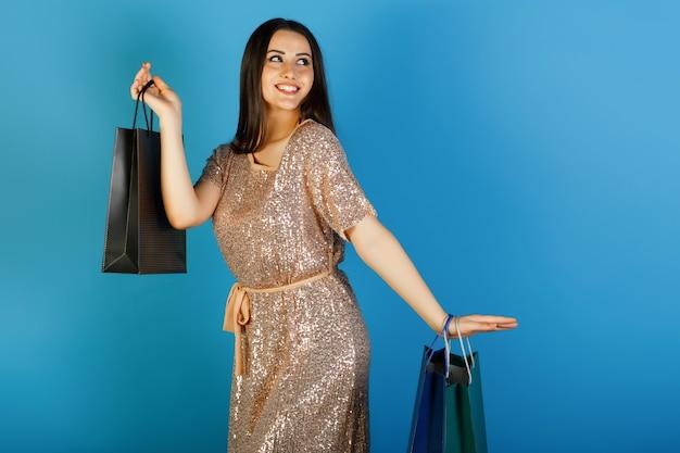 Meisjesklant die kleurrijke zakken houden en status geïsoleerd op blauwe studioachtergrond.