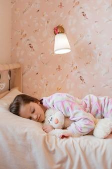 Meisjeslaap met haar favoriete stuk speelgoed thuis