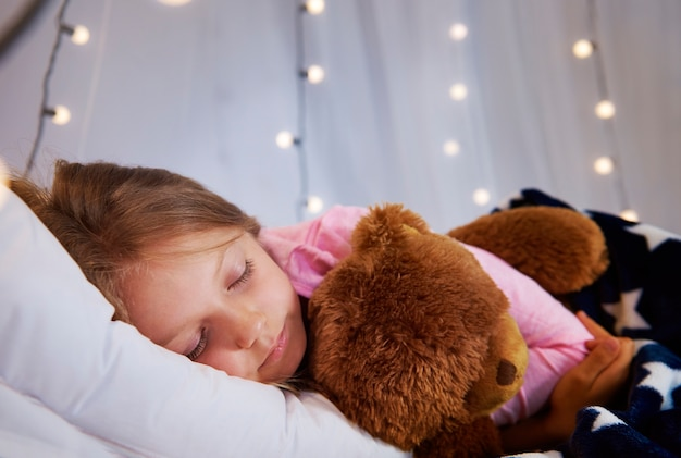 Meisjeslaap met teddybeer in haar slaapkamer