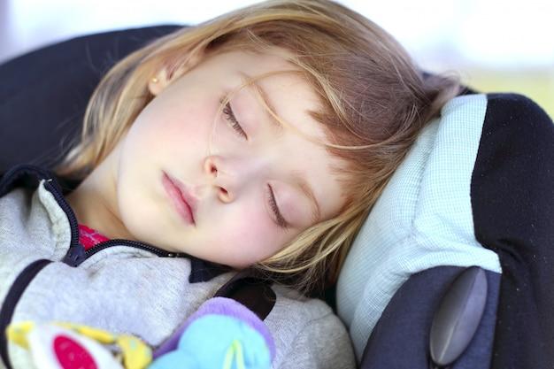 Meisjeslaap op de zetel van de kinderautoveiligheid