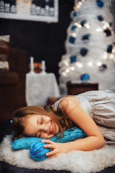 Meisjeslaap op een blauw hoofdkussen. het concept van het nieuwe jaar en merry christmas