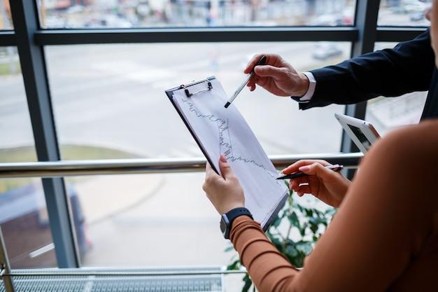Meisjesmanager in haar eigen kantoor vertelt een succesvol nieuw businessplan voor economische ontwikkeling aan haar leraar-mentorbaas. houdt een map met belangrijke documenten in zijn handen.