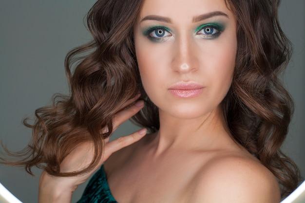 Meisjesmodel met make-up, close-upportret, met groene schaduwen. conceptomslag van een modeblad, make-up, krijsen of foto voor schoonheidssalons.