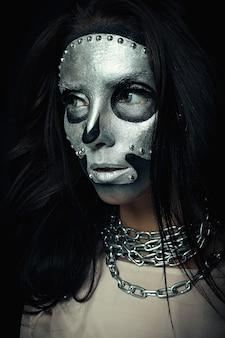 Meisjesmodel met zilveren maskerschedelverf op donkere achtergrond