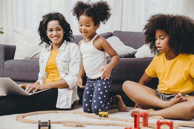 Meisjesmoeder werkt thuis met internetlaptopeffect van covid-19-virusziekte die graag bij haar kinderen blijft.