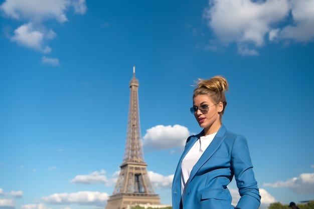 Meisjesreiziger in zonnebril, jasje in parijs, frankrijk. vrouw bij de toren van eiffel op blauwe hemel op zonnige dag. architectuur, attractie, mijlpaal. vakantie, reizend concept. mode, stijl, kopieer ruimte