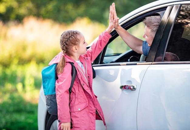 Meisjesschool die vijf geeft aan vader die in auto zit